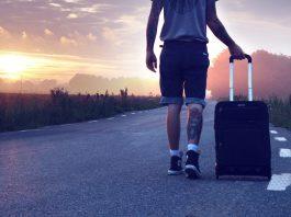 Mann mit Koffer im Sonnenuntergang