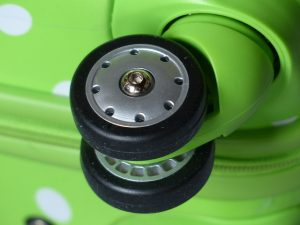Rollen eines grünen Koffers